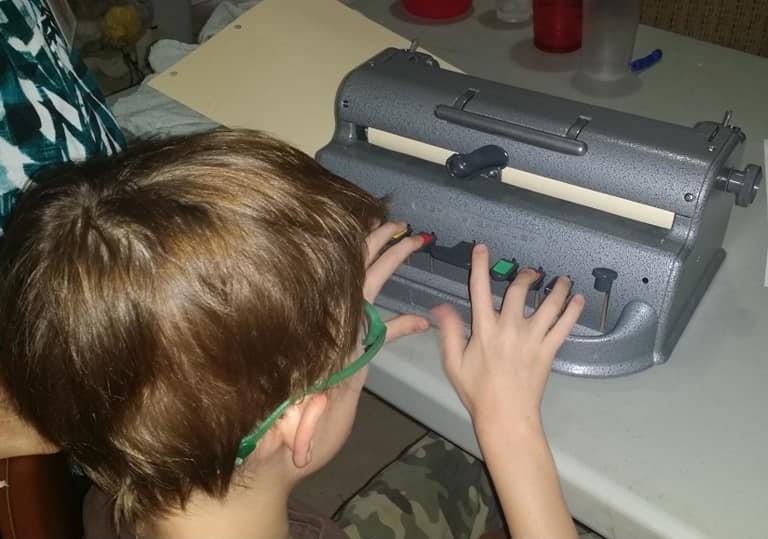 Joseph working on a Perkins Brailler